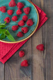 Raspberries and mint leaves in a plate Royalty Free Stock Photo