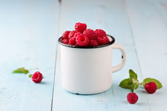 Raspberries in a mug Stock Images