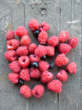 Raspberries on the old planking. Small group of raspberries and black-currant on the old planking Stock Images
