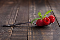 Raspberries on old spoon and mint on grunge wooden board. Natural healthy food. Still life photography Stock Photo