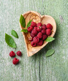 Raspberries in olive wood bowl shape of heart Stock Photo