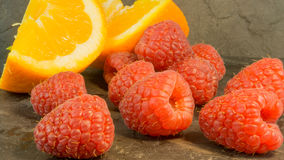 Raspberries and oranges on a dark background Royalty Free Stock Image