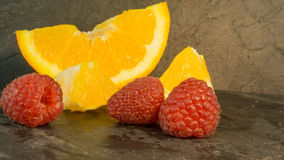 Raspberries and oranges on a dark background Stock Image
