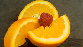 Raspberries and oranges on a dark background Stock Images