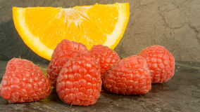 Raspberries and oranges on a dark background Royalty Free Stock Photos