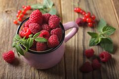 Red currant and raspberries. Raspberries in the pink mug on wooden table Stock Photos