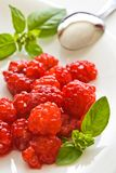 Raspberries on plate. Raspberries with green basil leaves on white plate royalty free stock photos