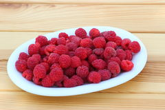 Raspberries in plate. Fresh raspberries in an oval white plate on a wooden table Stock Photography