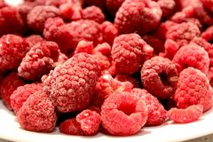 Raspberries on a plate. Red frosen raspberries whith ice on top lying on a white plate Stock Photos