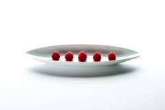 Raspberries. On a plate on white table Royalty Free Stock Photography