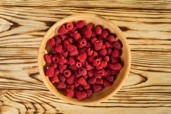 Raspberries in a plate,in wooden bowl,basket/bush branch/growing. Raspberries,raspberries background closeup photo,high resolution product,Delicious first class Stock Images