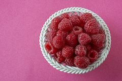 Raspberries in a porcelain bowl stock photo