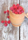 Raspberries in a pot on the wooden table. Fresh raspberries in a pot on the wooden table Royalty Free Stock Photos