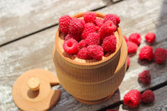 Raspberries in a pot on the wooden table. Fresh raspberries in a wooden pot on the table Royalty Free Stock Image