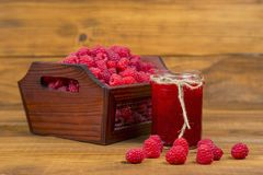 Raspberries and raspberry jam. On a wooden table Royalty Free Stock Photo