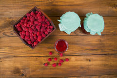 Raspberries and raspberry jam. On a wooden table Stock Photos