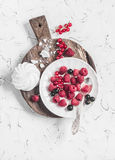 Raspberries, red and black currants, a meringue on a rustic cutting board. On bright background Royalty Free Stock Photos