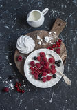 Raspberries, red and blackcurrants, a meringue, cream on a rustic cutting board Stock Photos