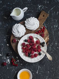 Raspberries, red and blackcurrants, a meringue, cream on a rustic cutting board Royalty Free Stock Images