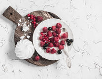 Raspberries, red and blackcurrants, a meringue on a rustic cutting board. On bright background Royalty Free Stock Image