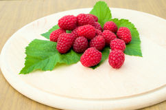 Raspberries are on a round wooden board. On a green leaf Royalty Free Stock Photo