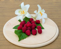 Raspberries are on a round wooden board. Raspberries and white lilies are on a round wooden board Stock Images