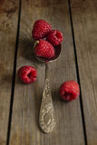 Raspberries in rustic kitchen setting with wooden background wit Stock Photography