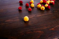 Raspberries scattered on a dark background. Red and yellow raspberries. Wooden background Royalty Free Stock Photos