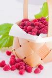 Raspberries in a small basket. Fresh fruits raspberries in a wooden little basket on a white table Stock Photo
