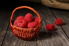 Raspberries in a basket on an old table Stock Photography