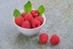 Raspberries. Small White China Bowl Filled with Fresh Raspberries on a Slate Board Royalty Free Stock Photos