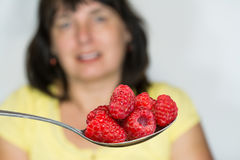 Red juicy raspberries on spoon and blurred woman in background royalty free stock image
