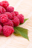 Raspberries on straw mat Stock Photos