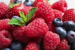 Raspberries, strawberries, blueberries and mint. Closeup royalty free stock photography