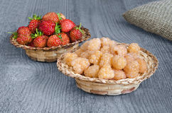 Raspberries and strawberries in wicker baskets, on wooden surface. Raspberries and strawberries in baskets on gray blue wooden surface. Selective focus Royalty Free Stock Images