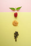 Raspberries, sugar, a mint leaf and a handful of green tea on a Royalty Free Stock Photography