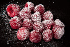 Raspberries with a sugar powder on a black Royalty Free Stock Photos