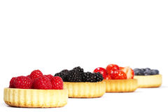 Raspberries in tartlet cake in front of other tart Stock Photos
