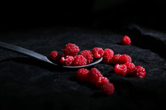 Raspberries in a teaspoon. Black background Stock Photography