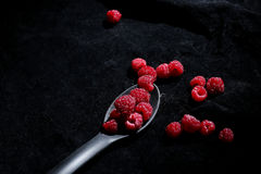 Raspberries in a teaspoon. Black background Royalty Free Stock Images