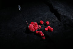 Raspberries in a teaspoon. Black background Royalty Free Stock Image