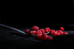 Raspberries in a teaspoon. Black background Stock Photos