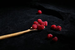 Raspberries in a teaspoon. Black background Stock Photo