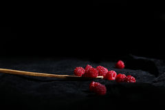 Raspberries in a teaspoon. Black background Royalty Free Stock Photo