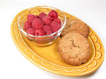 Raspberries & Two Cookies. A snack of raspberries and two cookies rests on a yellow dish stock photography