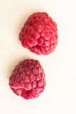 Raspberries. Two red raspberries stacked on a beige background Royalty Free Stock Photography