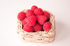 Raspberries in a white basket closeup. Group of beautiful pink raspberries in a white basket closeup Stock Image