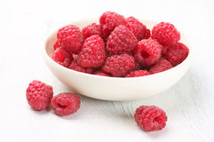 Raspberries in white bowl. Fresh raspberries in white bowl on white rustic wooden background Royalty Free Stock Images