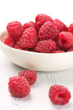 Raspberries in white bowl. Fresh raspberries in white bowl on white rustic wooden background Stock Photography
