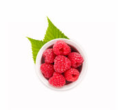 Raspberries in a white ceramic bowl. Ripe and tasty raspberries isolated on white background. Top view Royalty Free Stock Photography